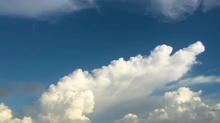 レイヤード : Time-lapse of the blue sky with the white big cloud moving and transforming with the wind during sunset 動画素材