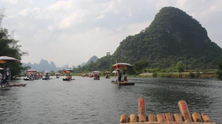 flutuador : Bamboo raft on Yulong river with ancient stone arch bridge in Yangshuo Guilin Guangxi China.