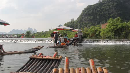 flutuador : Bamboo raft moving upriver using a special mechanism on Yulong river in Yangshuo Guilin Guangxi China.