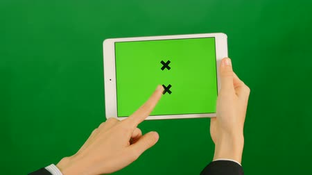 editor : Businesswoman using a blank green screen tablet on green background. Front view.
