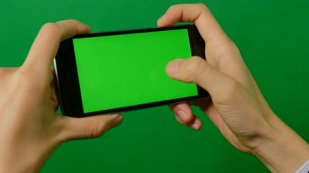 editor : Businesswoman using a blank green screen mobile phone on green background. Front view. Stock Footage