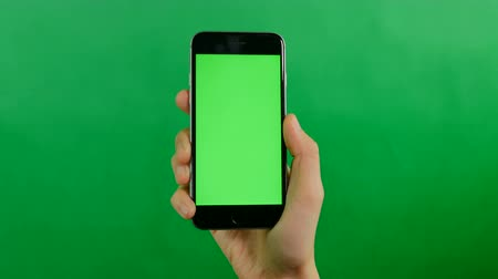 editor : Businesswoman holds a blank green screen mobile phone on green background. Front view. Stock Footage