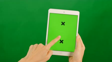 acessibilidade : Businesswoman using a blank green screen tablet on green background. Front view.