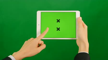 přenosný : Businesswoman using a blank green screen tablet on green background. Front view.