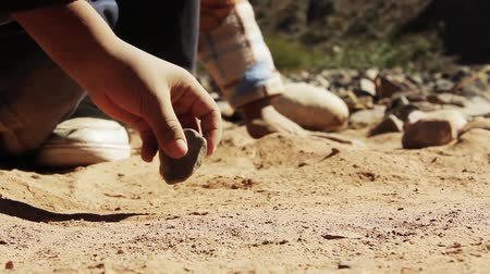 tık : Children cleaning the ground from the dry soil to play with stones