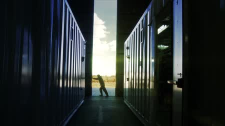 Man Opening Door Of A Container Warehouse At Sunset. Stock mozgókép