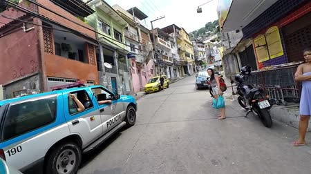 Рио : Driving inside of the slum (favela) with police car , people and mototaxi in Rio de Janeiro, Brazil