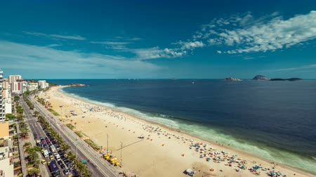 brezilya : Street traffic with people relaxing on the Beach at afternoon sun in Rio De Janeiro, Brazil. Clouds dynamic Time Lapse from high angle Stok Video