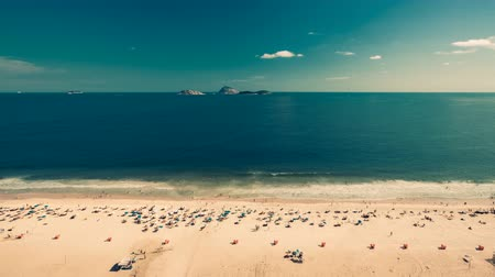brezilya : People relaxing on the Beach in tropic climate of Rio De Janeiro, Brazil. High angle Time Lapse with clouds dynamic