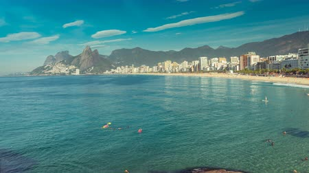 Рио : Ipanema Beach panning time lapse with people swimming in the ocean. Rio De Janeiro, Brazil Стоковые видеозаписи