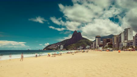 Рио : Bright sun on Ipanema Beach with people walking against Rio de Janeiro skyline in Brazil. Time lapse with clouds dynamic