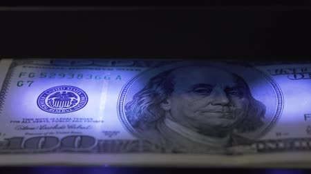 filigran : 100 dollar bill under ultraviolet light, checking machine