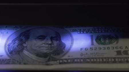 filigran : 100 dollar bill under ultraviolet light machine Stok Video