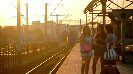 očekával : Belaya Tserkov, Ukraine - July 31, 2015. Blue train locomotive arrives at the station, there are people on the platform, blurry young women Dostupné videozáznamy