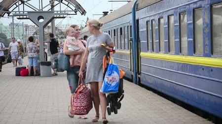 mourners : Train Station, Bila Tserkva, Ukraine -July 26, 2015: Young woman with shopping bags  and  woman with a child go on the platform the train station and waving good-bye Stock Footage