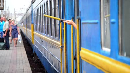mourners : Train Station, Belaya Tserkov, Ukraine - July 29, 2015.Hand holding a yellow flag sign of readiness for shipping blue train car Stock Footage
