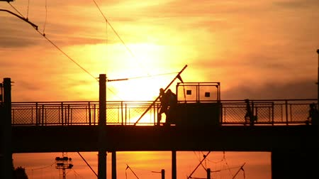 traverse : Black silhouettes of people walking on the bridge, cross the bridge with their luggage during sunset, sunrise orange sky background with the sun
