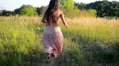 brown dress : brunette woman with long hair in a pink dress and running on the road in a field