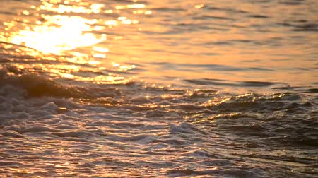 ondas : The sun is reflected in the waves of the sea during sunset and sunrise close up