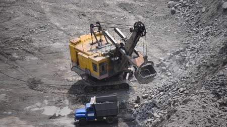 buldozer : Huge Yellow Excavator Pickup Loading Stones Into a Truck , Trucks Driver Standing Next, and a man standing next to the waiting, On a Sunny Day, Top View, Different Sizes, With Sound,