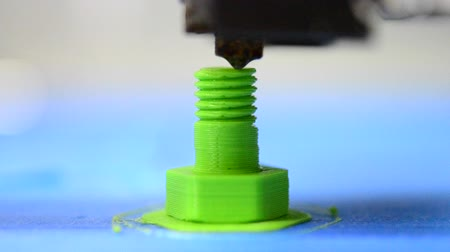 impressão digital : HD 1080 3D printer prints from the plastic figure in the form of a bolt closeup. 3D printer makes or printing bolt model, screw green colour close-up on blue flat surface Stock Footage