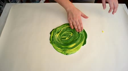 gruel : Mixing paint yellow with green and hands smearing on white surface.Creative activity.Top view of flat line. Smooth and slow motion hands.ArtTherapy.Creative color mixing close-up HD 1080.Painting hand