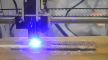 impressão digital : 3d printer laser beam burns the pattern close-up on a wooden board. Industrial Modern technological background. Laser blue 3d printer moves on a wooden surface burns words, pictures