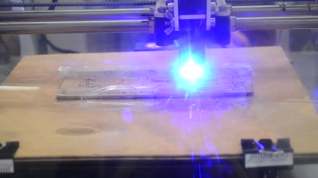 impressão digital : Timelapse 3d printer laser beam burns the pattern close-up on a wooden board. Industrial Modern technological background. Laser blue 3d printer moves on a wooden surface burns words, pictures