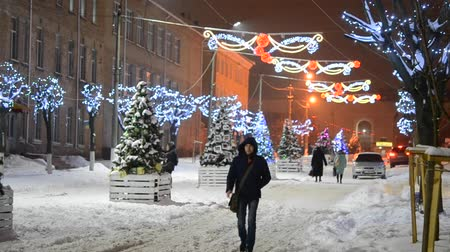 světlomety : People townspeople walk on a snow-covered street decorated with lights for the New Year and Christmas