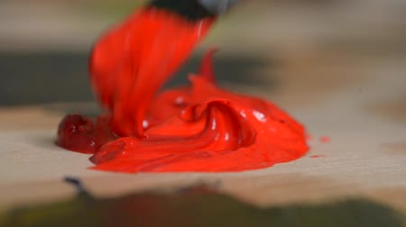 expressionism : Blending red oil paint with a brush close-up