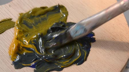 művésziesség : Mixing the oil paint yellow and blue in the palette close-up