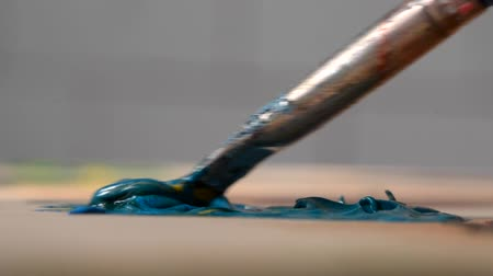 oilpaint : Paint blue are mixed with a brush close-up. Strongly blurred background