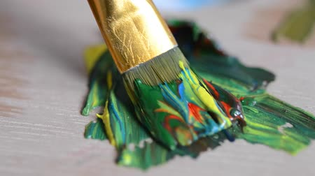 pędzel : Mixing the oil paint yellow and green with red and blue in the palette close-up Wideo