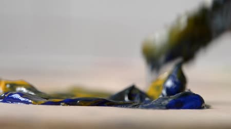 artsy : Mixing the oil paint yellow and blue in the palette close-up. Strongly blurred background Stock Footage