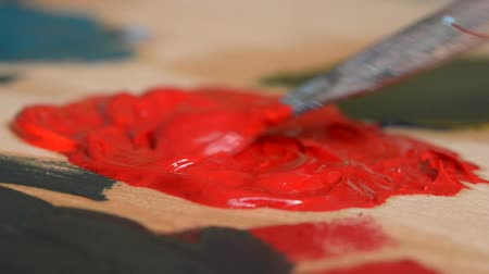 oilpaint : Paint red are mixed with a brush close-up