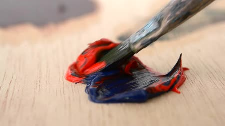 oilpaint : Mixing the oil paint blue and red in the palette close-up