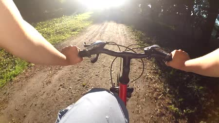 управлять : Bicycle riding on a bike in a summer sunny day dirt road close-up