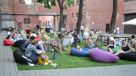 cityspace : Kiev, Ukraine, Festival Street Food - July 23 2017: Many people are sitting and relax rest on colorful seat-bags. Stock Footage