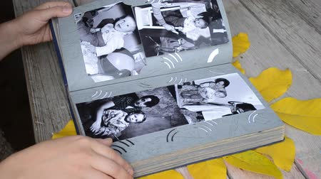 atrás : Girl leafing through a photo album with old photos which lies on the table with leafy leaves of a tree close-up