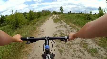 управлять : Man riding a bicycle in a field on a day along the dirt path. POV. The shooting was conducted by an action camera