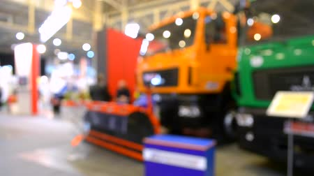 vago : Blurred Background Many cars trucks lorry inside the exhibition pavilion and people walk around with interior lighting Stock Footage
