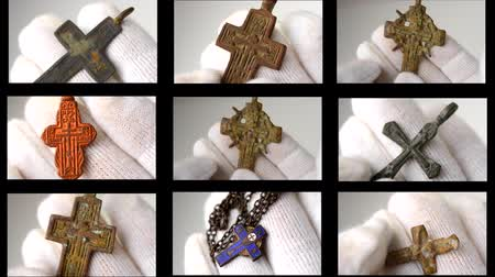 антиквариат : Archaeological find Christian pectoral cross close-up in hands with white gloves. Crucifix archaeological find.