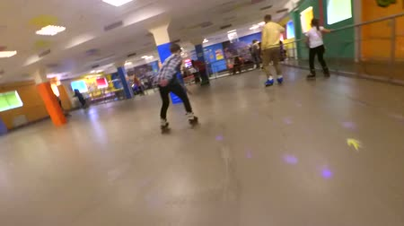 paten yapma : Bila Tserkva, Ukraine January 21, 2018: Slow motion. Person roller-skating on inside rollerdrom. Many people of children and adults go roller-skating on indoors. Point of view, pov mtb. Low Angle View Stok Video