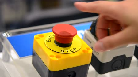 emergency stop : The person clicks a finger at the big red Stop button. Control buttons panel close-up.
