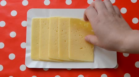 cheese slices : Person taking slices of cheese with a red surface in a white pea tablecloth. Close-up top view. Food chef cook Stock Footage