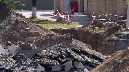 reddish : Pieces of broken asphalt and a dug pit with a protective red-white ribbon at the construction site. Replacement of pipes for heating of a heating main near an apartment house Stock Footage