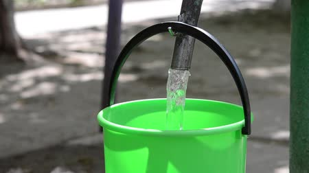 full bucket : A man pours water in a plastic bucket. Concept of clean drinking water