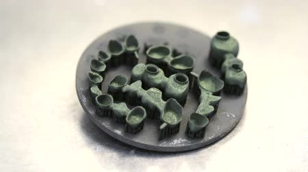 titanium : Object printed on metal 3d printer after heat treatment. Dental crowns created in laser sintering machine close-up. DMLS, SLM, SLS technology. Concept of 4.0 industrial revolution. Progressive modern