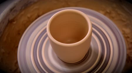 clay pot : Vase from fresh clay turn twirl potters wheel. Sculptor in workshop makes jug out of clay closeup. Master crock. Potters work close-up. Workshop pottery. Handmade. Craft. Traditions. Seamless loop Stock Footage