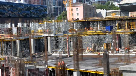 reinforced concrete : Many builder works orange protective uniform at against background of construction site high-rise buildings. Construction workers, work hard to build new building for expensive apartment and office.